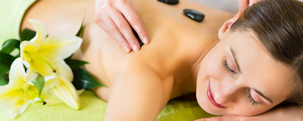 Beautiful woman having a wellness hot stone back massage